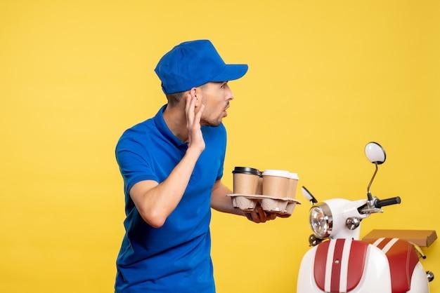 Vue avant male courrier tenant le café de livraison sur la couleur jaune travailleur service travail émotions travail livraison vélo uniforme