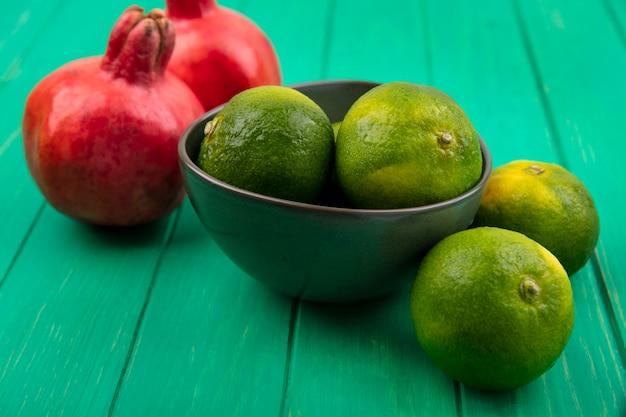 Vue avant des mandarines dans un bol et des grenades sur un mur végétal