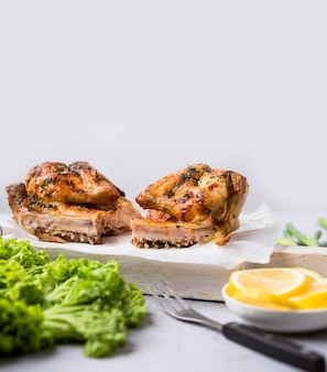 Vue avant des moitiés de poulet entier cuit au four avec salade