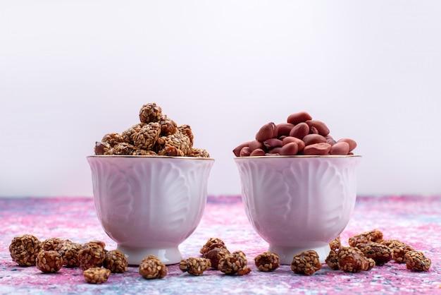 Vue avant des noix collantes douces à l'intérieur des assiettes violettes