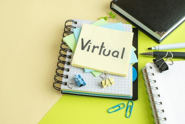 Vue avant de la note écrite virtuelle avec des autocollants et le bloc-notes sur la surface colorée du cahier couleur salaire emploi bureau business college school money