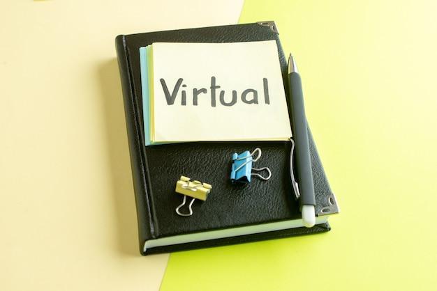 Vue avant de la note écrite virtuelle avec bloc-notes noir et stylo sur la surface verte cahier salaire emploi couleur école bureau bureau business