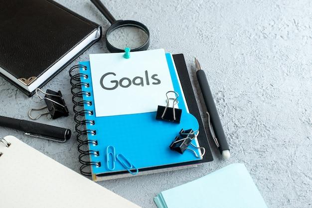 Vue avant objectifs note écrite avec bloc-notes et stylo sur fond blanc
