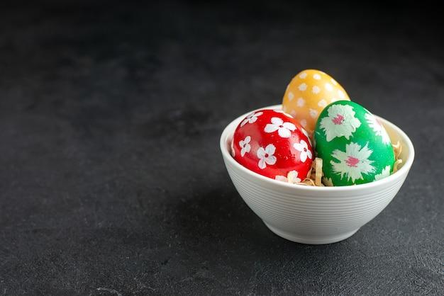 Vue avant des oeufs de pâques colorés à l'intérieur de la plaque sur fond sombre concept horizontal couleur printemps fleuri coloré
