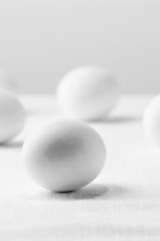 Vue avant des œufs de poule blanche sur table