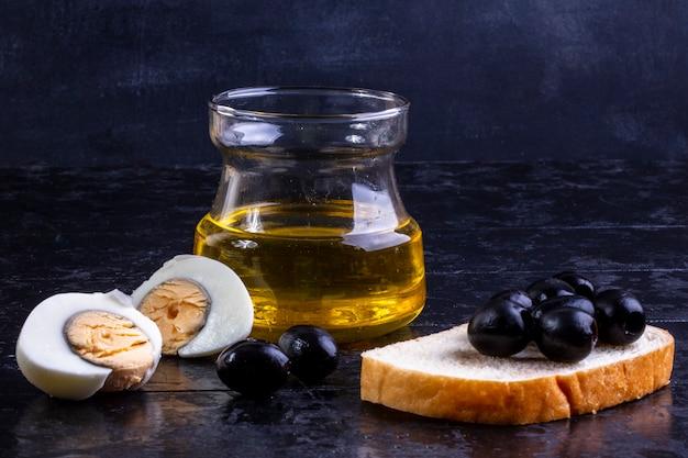 Vue avant, olives noires, sur, tranche pain, à, oeuf dur, et, huile olive, dans, a, pot, sur, noir
