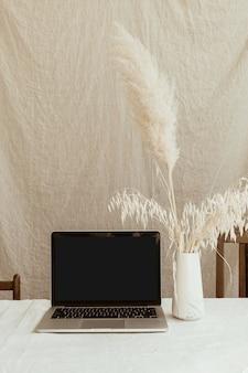 Vue avant de l'ordinateur portable à écran blanc et de l'herbe de la pampa moelleuse contre le mur de lin beige pastel.