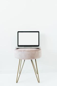 Vue avant de l'ordinateur portable écran maquette vierge sur tabouret élégant sur blanc