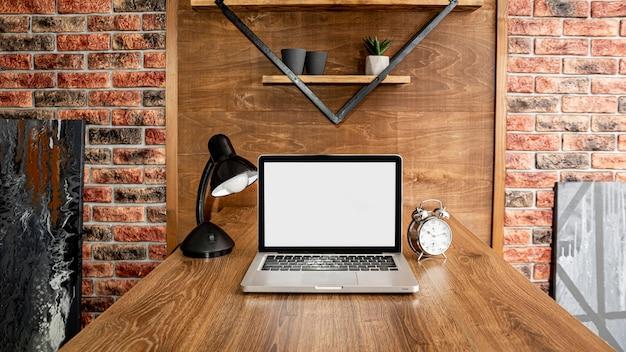 Vue avant de l'ordinateur portable sur l'espace de travail de bureau avec lampe