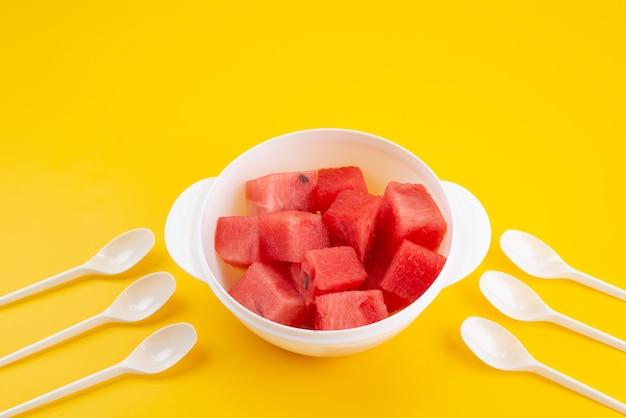 Une vue avant de la pastèque fraîche en tranches à l'intérieur d'une plaque en plastique blanc sur un bureau jaune