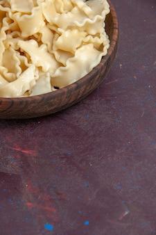 Vue avant de la pâte crue en tranches à l'intérieur de la plaque brune sur un espace violet foncé