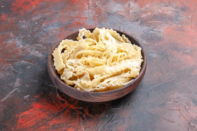 Vue avant de la pâte crue en tranches à l'intérieur de la plaque sur la surface sombre de la pâte de pâtes alimentaires sombres crues