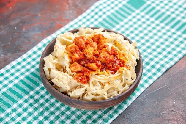 Vue avant de la pâte cuite savoureuse avec du poulet et de la sauce sur les pâtes de plat de repas de bureau sombre