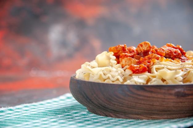 Vue avant de la pâte cuite savoureuse avec du poulet et de la sauce sur les pâtes de plat de repas de surface sombre