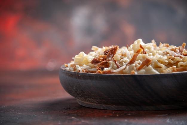 Vue avant de la pâte cuite en tranches avec du riz sur la pâte de plat de pâtes surface sombre