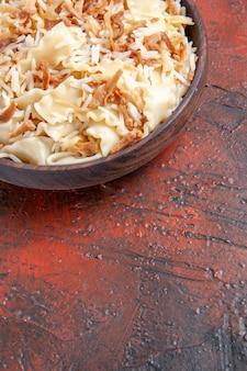 Vue avant de la pâte cuite en tranches avec du riz sur le plat de pâtes de surface sombre repas de pâte