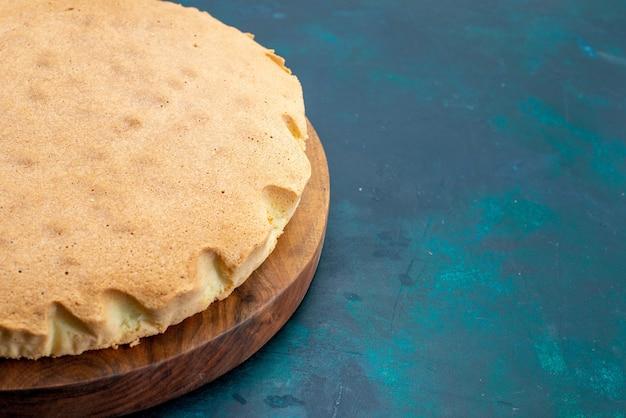 Vue avant de la pâte à gâteau ordinaire cuite ronde formée sur le gâteau mural bleu foncé cuire la tarte à la pâte à sucre sucrée
