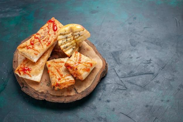 Vue avant de la pâte pita roulée en tranches avec garniture de viande et sauce sur un bureau bleu foncé