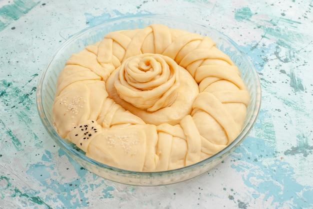 Vue avant de la pâte à tarte crue ronde formée sur la surface bleue tarte biscuit gâteau cru sucré