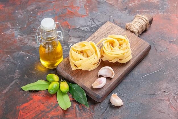 Vue avant des pâtes crues avec de l'huile et de l'ail sur la pâte de pâtes de surface foncée crue