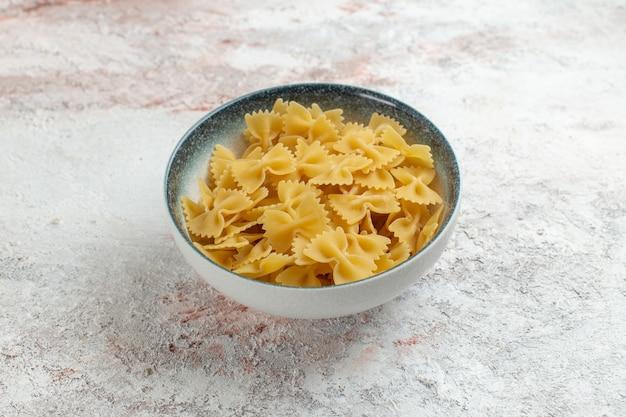 Vue avant des pâtes italiennes crues peu formées sur une surface blanche