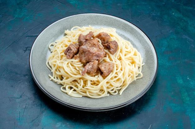 Vue avant des pâtes italiennes cuites avec de la viande en tranches à l'intérieur de la plaque sur la surface bleue pâtes italie repas repas dîner viande pâte