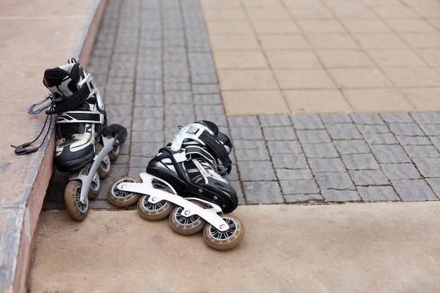 Vue avant des patins à roues alignées sur la chaussée avec copie espace