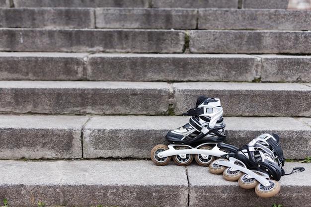 Vue avant des patins à roues alignées dans les escaliers avec copie espace
