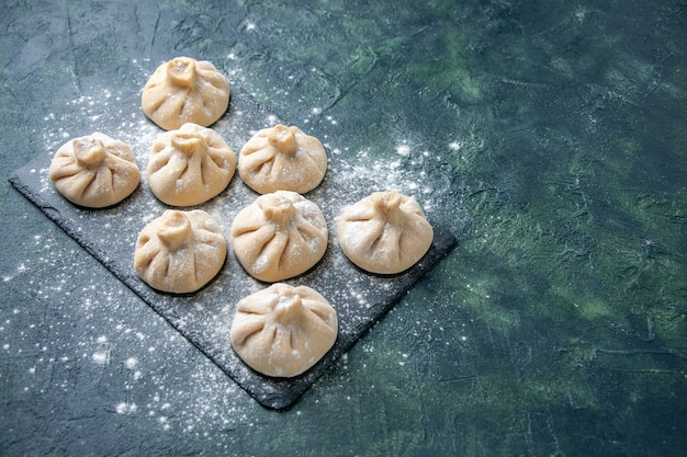Vue avant de petites boulettes crues avec de la viande à l'intérieur sur fond sombre plat de couleur cuisine crue cuisine repas farine de viande de la pâte