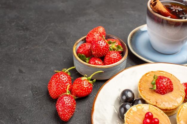 Vue avant de petites crêpes délicieuses avec des fruits et une tasse de thé sur un gâteau à tarte de surface gris foncé