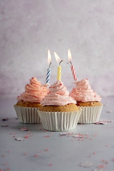 Vue avant des petits gâteaux d'anniversaire avec glaçage et bougies allumées