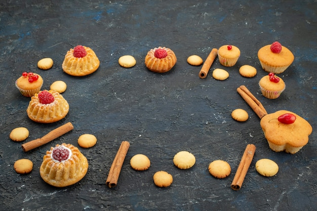 Vue avant de petits gâteaux délicieux avec des biscuits à la crème à la cannelle sur le bureau sombre gâteau biscuit dessert fruit berry