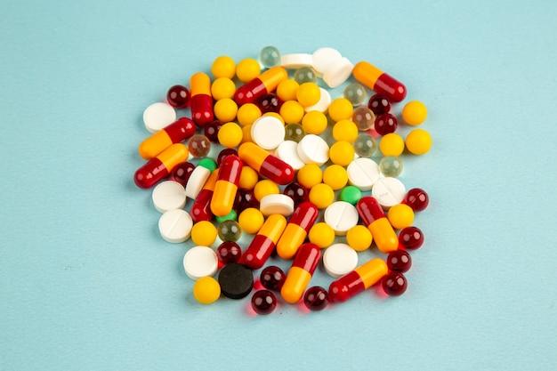 Vue avant des pilules colorées sur la surface bleue couleur de l'hôpital de la santé covid- virus de médicament de laboratoire scientifique pandémique