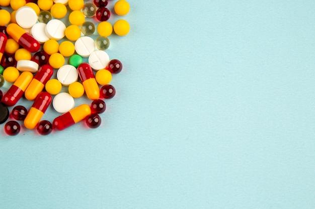 Vue avant des pilules colorées sur la surface bleue couleur de l'hôpital de la santé covid- virus de médicament de laboratoire scientifique