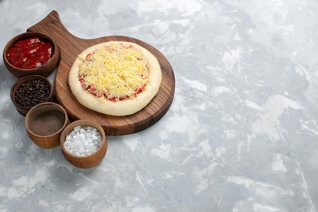 Vue avant de la pizza crue avec différents assaisonnements sur un bureau blanc