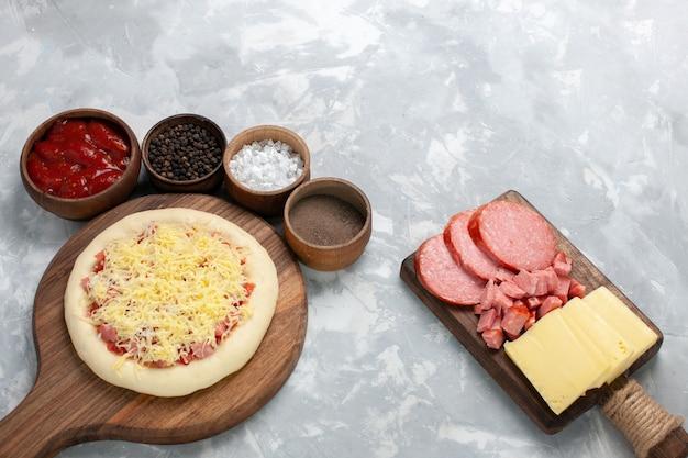 Vue avant de la pizza crue avec du fromage et des assaisonnements sur blanc