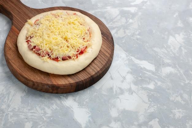 Vue avant de la pizza crue avec du fromage sur blanc