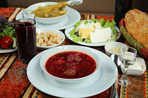 Vue avant plat ukrainien traditionnel bortsch dans une assiette avec du fromage et du pain tandoor avec un verre de vodka et de jus sur la table
