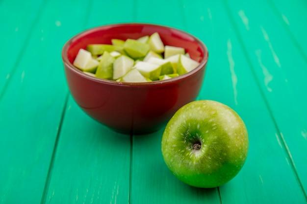 Vue avant de la pomme verte avec des tranches hachées sur un bol rouge sur une surface verte