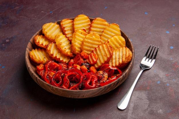 Vue avant de pommes de terre au four avec des légumes cuits à l'intérieur de la plaque sur l'espace sombre