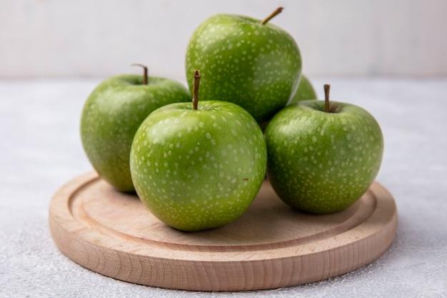 Vue avant des pommes vertes sur un support sur fond blanc