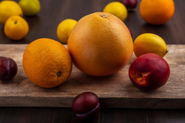 Vue avant de la prune au pamplemousse citron orange et pêche sur une planche à découper sur un fond en bois