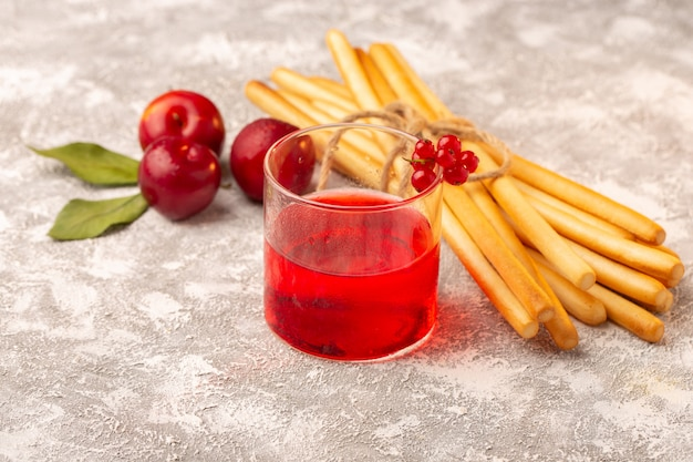 Vue avant des prunes aigres fraîches avec du jus de prune rouge