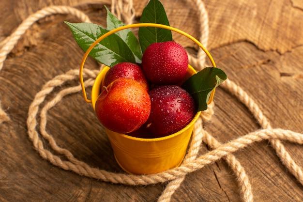 Vue avant des prunes moelleuses fraîches à l'intérieur du panier jaune avec des cordes sur un bureau en bois
