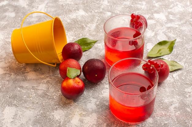 Vue avant des prunes rouges fraîches avec du jus de prune