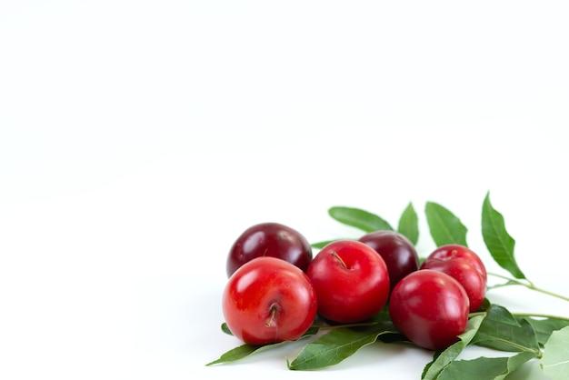 Une vue avant des prunes rouges moelleuses et aigres sur un bureau blanc