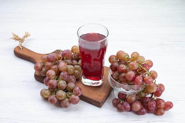 Vue avant des raisins frais aigres avec du jus rouge sur un bureau blanc léger boisson de jus de fruits frais moelleux