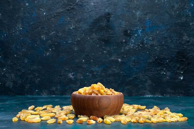 Vue avant des raisins secs à l'intérieur et à l'extérieur du pot brun sur le bureau bleu.