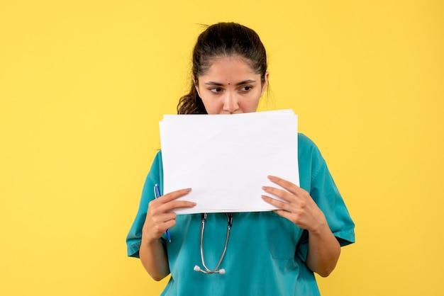 Vue avant réfléchie femme médecin avec des documents debout sur fond jaune