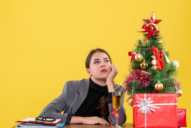 Vue avant réfléchie fille assise au bureau mettant la main